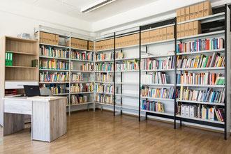 Ein Foto der Bibliothek. Zwei Regalwände mit Büchern. Ein Schreibtisch.