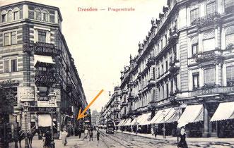 """Die Prager Straße um 1930. Das Eck-Gebäude links (Cafe Hülfert, an der Kreuzung  Prager / Sidonienstraße) war Nr. 48, gleich links dahinter Prager Straße Nr. 44, der  erste Firmensitz """"Charlotte Meentzen - Institut für Schönheitspflege""""  (Pfeil)."""