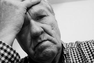 Deprimiert blickender älterer Mann stützt seinen Kopf in die Hand