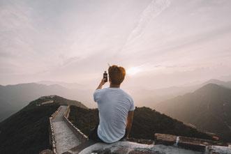 Mann sitzt mit Smartphone auf der chinesischen Mauer