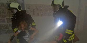 Zwei Feuerwehrleute unter Atemschutz bringen ein verletztes Kind aus der Gefahrenzone.  Foto: Frank Gehrmann