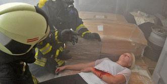 Feuerwehrmänner retten in dem verqualmten Gebäude eine verletzte Frau. Foto: Frank Gehrmann