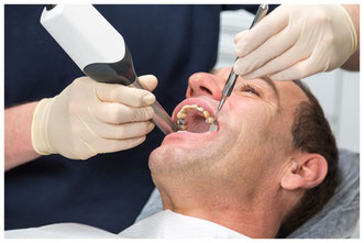 Dentist scanning patient's teeth with CEREC scanner © ikonoklast_hh