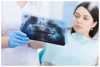 Doctor talking with patient and showing a radiograph in stomatology clinic © 4frame group