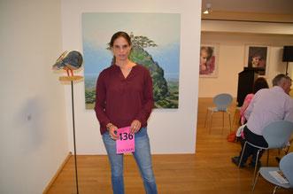 Christina Steinhausen mit ihrer Auktionskarte vor zwei Kunstwerken.