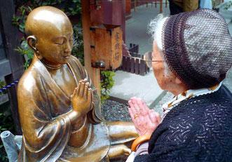 innig unterhält sich diese Japanerin mit Ihrem Buddha