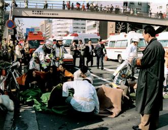 1995年3月、地下鉄サリン事件で有毒ガスにより倒れ、路上で手当てを受ける乗客ら=東京都中央区築地(共同)