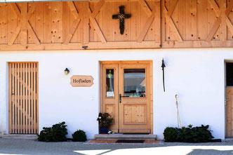 Eingangstür zum Hofladen mit Kreuz über der Tür