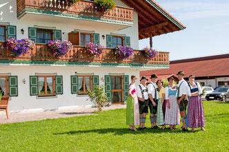 """Die ganze Familie - in Dirndl und Lederhose - vor dem Bauernhof """"Zum Marx"""" in Obersöchering."""