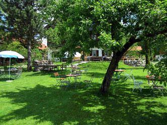 Sonnige Wiese mit Obstbäumen, Tischen und Stühlen