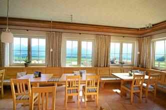 Gaststube mit Blick aus den Fenstern auf die Berge