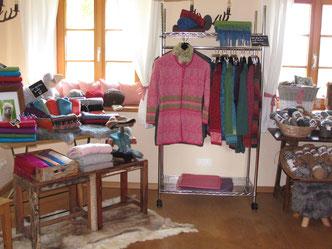 Innenansicht des Hofladens mit einer Auswahl an Jacken, Pullovern und Mützen aus Alpakawolle