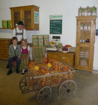 Familie in der Verkaufs-Hofscheune mit Leiterwagen voller Kartoffelsäcke, Waage und Verkaufsvitrine