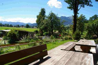 Holzsitzgruppe auf der Terrasse des Cafés mit Blick auf den Obstgarten, Lenggrieser Berge und Brauneck