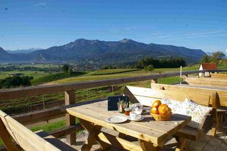 Terrasse mit gedecktem Tisch vor Bergkulisse mit blauem Himmel und grünen Hügeln