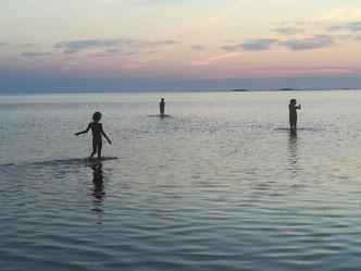 Drei Menschen baden in der Nordsee