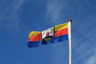 Nordfriesland-Fahne mit Pellworm-Wappen weht im Wind