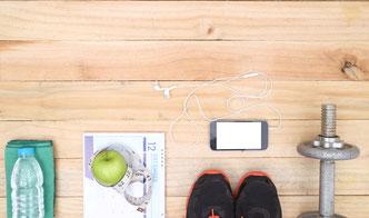 Tisch mit Sportgeräten, Laufschuhen, Smartphone und Wasserflasche