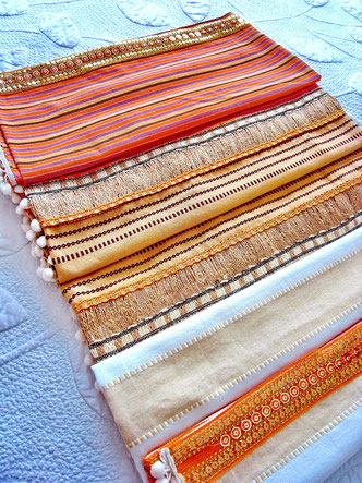 Aerial view of three-piece, orange, white and sandy striped, flat-weave, Indian cotton throw with white pom-pom trim and thick joining ribbons of orange metallic sequence and natural jute