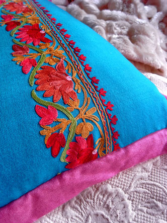 Detail of berry-pink pashmina, folded edge & woolen floral embroidery on cushion cover