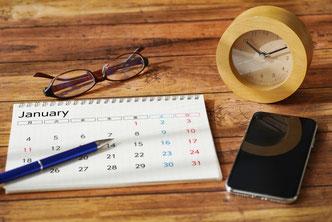 デスクに置かれたカレンダー。ボールペン。リーディンググラス。スマホ。置時計。