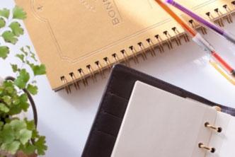 リング式ノートブックの上に電卓と万年筆。