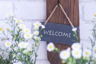 壁にかかった黒板のウェルカムボード。周りを囲む白の小花たち。