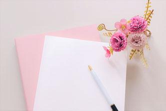 ピンクとホワイトの2冊のノートとボールペン。花びんに活けられたアレンジメントフラワー。