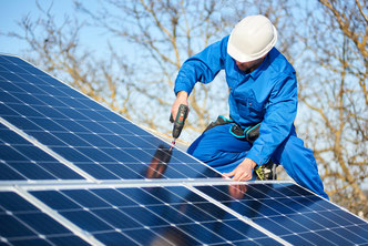 Man putting solar panels on house.