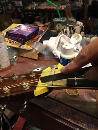 ナットにギター弦がはまる溝を掘る作業を横から見たシーン