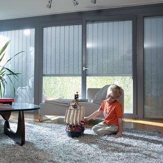 Bub spielt im Wohnzimmer vor einem Tageslichtrollladen S_Onro