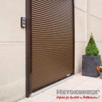Silberner Sicherheitsrollladen an modernem rotem Haus mit Pool