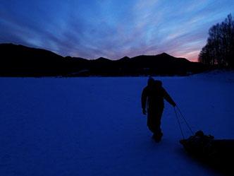 ファンタジックな朝焼けの中、釣り道具やテント、食べものにビールなど荷物満載のスレーをひいてお目当ての場所へ。