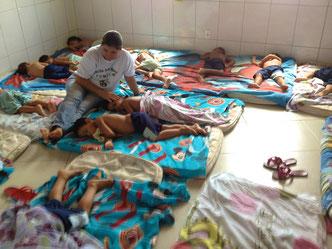 Kinder werden mittags in den Schlaf gestreichelt