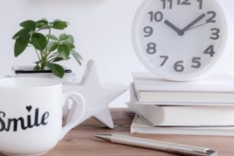 デスクに摘まれた本と置時計。観葉植物の鉢植え。マグカップとボールペン。