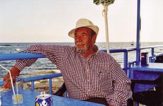 Alter Mann mit Strohhut und kariertem Hemd im Strandcafé, lehnt einen Arm über die Balustrade und blickt in die Weite.