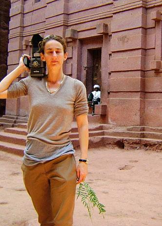 Junge schlanke Frau mit kurzen dunklen Haaren, Augen geschlossen, Kamera auf der Schulter
