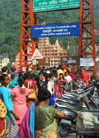 Auf der schwankenden, schmalen Hängebrücke über den Ganges drängen sich die Menschen wie Sardinen im Schwarm.