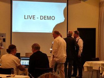 """Menschen im Gespräch vor einer Leinwand mit dem Text: """"Live Demo"""""""