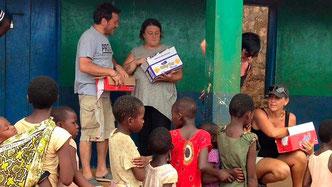 Lilian Sora (in piedi al centro) e Mariangela Beltrame, contitolare del ristorante pizzeria Karen Blixen (seduta in basso a destra) distribuiscono alcuni regali ai bimbi di Chakama