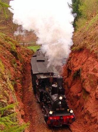 """Mächtig unter Dampf zieht die """"Speyerbach"""" den Museumszug  vor Elmstein durch eine enge Schlucht."""