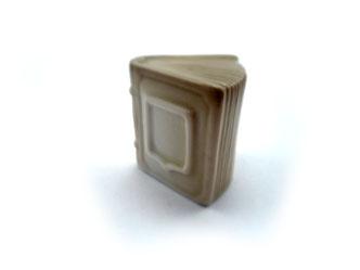 Dedal de porcelana, libro marrón con escudo.