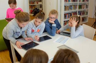 Gruppe von Schüler/-innen mit QR-Code und Tablets