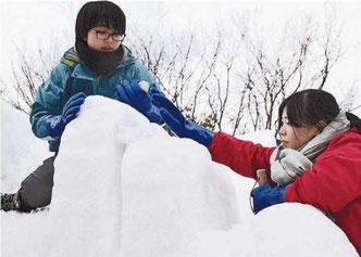 水を混ぜた雪で雪像の形を整える札幌平岸高の生徒(1月25日北海道新聞より)