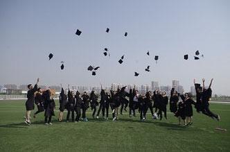 Doktoranden werfen ihre Hüte in die Luft