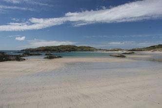 breiter weißer Sandstrand, Derrynane Beach Ring of Kerry in Irland mit ein paar flachen, vom Meer umspülten Felsen im Hintergrund und blauem Himmel mit weißen Wolken