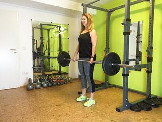 Trainerin Karin Grünauer mit Langhantel im Trainingsraum