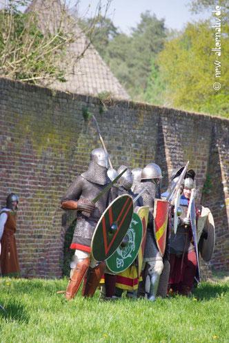 Hier sieht man mittelalterliche Kämpfer in Rüstungen vor einer Mauer.