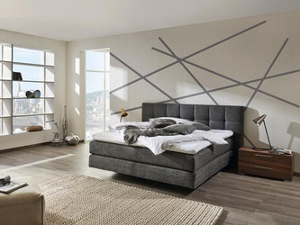 Dicke Polsterungen lassen das Rückenteil des Bettes der Kollektion mySUITEhome von Hülsta wie ein bequemes Sofa wirken. Foto: www.huelsta.de
