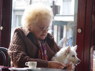 Seniorin mit Hund im Café